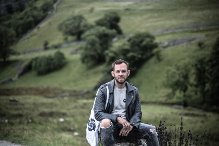 Portrait of man sitting on rock against landscape