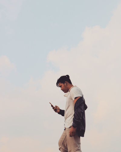 Side view of man using mobile phone against sky while music on