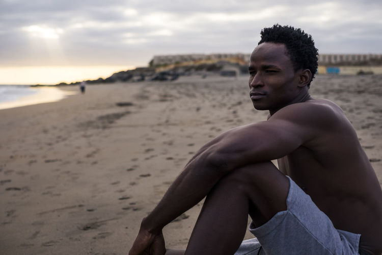 portrait of beautiful black man athlete resting sitting down at the beach with sunset in background. nice body for healthy lifestyle and daily exercises like fitness and running 25-29 Years Coastline Beach Cloud - Sky Contemplation Focus On Foreground Land Leisure Activity Lifestyles Muscles Nature One Person Outdoors Portrait Real People Sand Sea Shirtless Shore Sitting Sky Son Water Young Adult Young Men