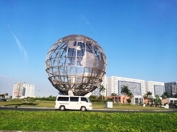 Van in front of globe structure against sky