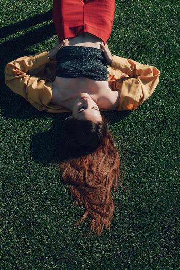 High angle view of woman sleeping on grass