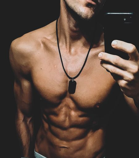 Midsection Of Shirtless Young Man Taking Selfie With Smart Phone While Standing In Darkroom
