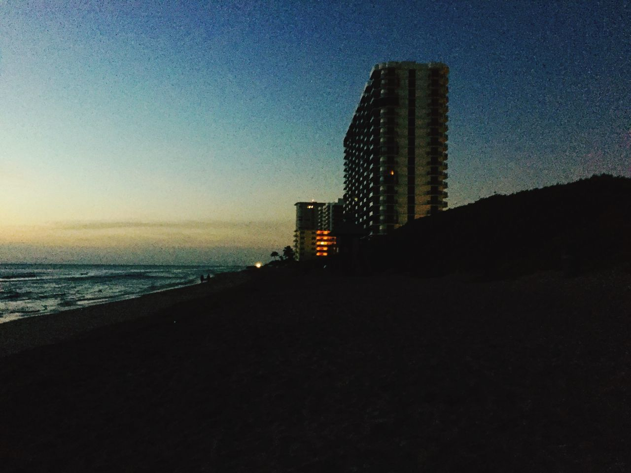 architecture, built structure, sea, sky, building exterior, skyscraper, beach, no people, clear sky, outdoors, nature, modern, city, night, water, beauty in nature