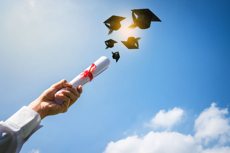 Low Angle View Of Hand Holding Degree With Mortarboard Against Sky