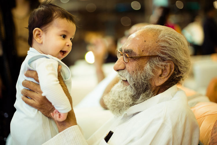 Side view of grandfather carrying grandson while sitting on sofa at home