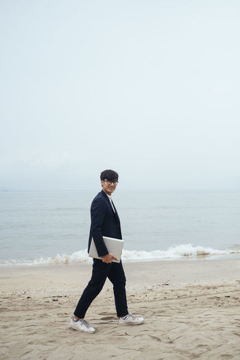 Full length of young man standing on beach against sky