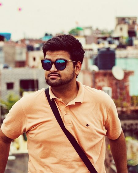 Young man wearing sunglasses standing in city