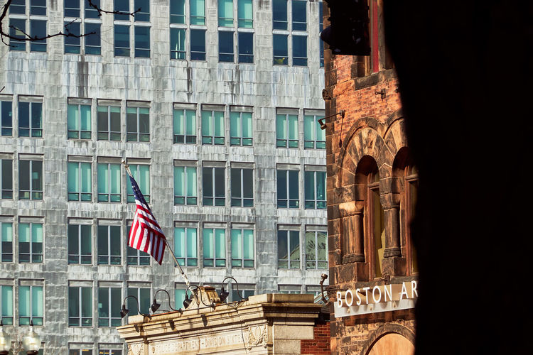 Low angle view of american flag on building in city