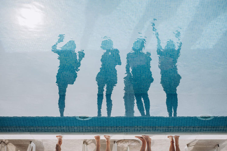 Reflection of people standing by swimming pool