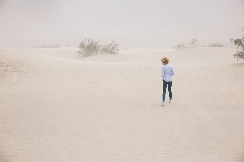 Arid Climate Arid Landscape Beauty In Nature Curly Hair Day Death Valley Death Valley National Park Desert Dunes Full Length Girl Landscape Nature One Person Outdoors People Real People Rear View Sand Dune Sand Storm Sky Standing Storm Tree Walking