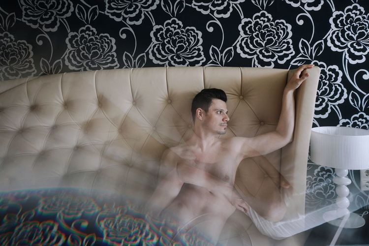 Double exposure of shirtless man against headboard