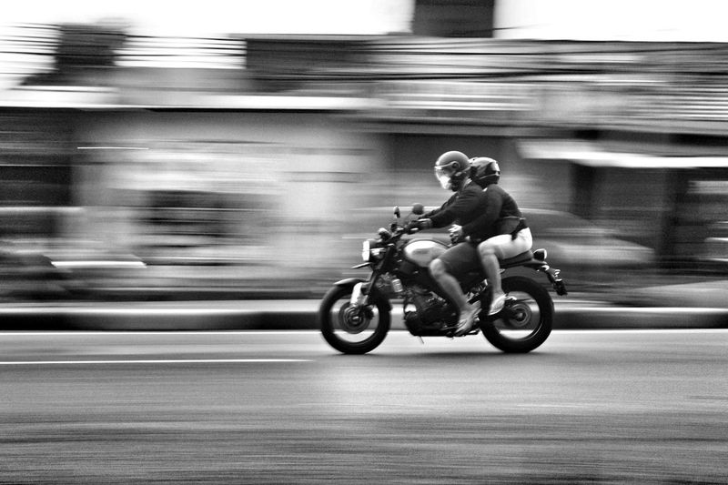 Blurred motion of man riding motorcycle on street