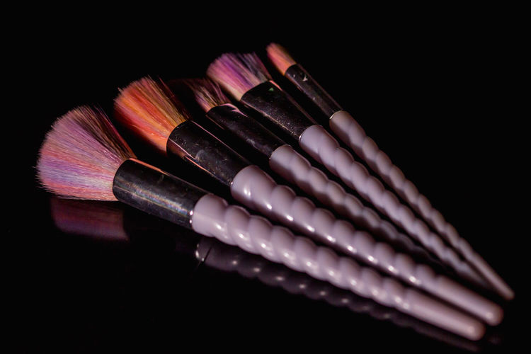 Close-up of colored pencils over black background