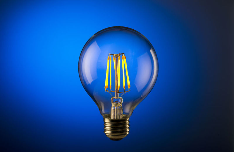 Round light bulb on blue Light Bulb Lighting Equipment Blue Electricity  Illuminated Filament Studio Shot Single Object Colored Background Glowing Blue Background Indoors  Fuel And Power Generation No People Close-up Energy Efficient Lightbulb Luminosity Copy Space Electric Light