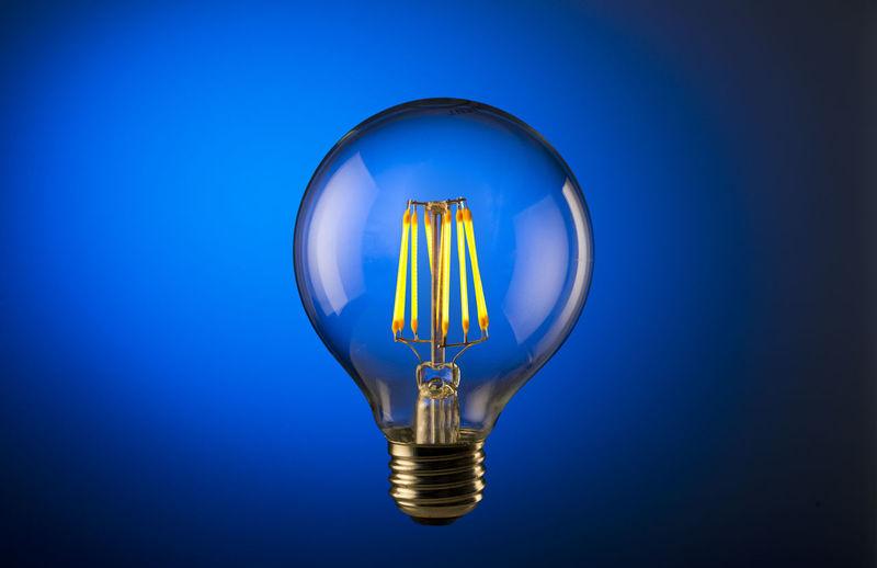 Illuminated light bulb against blue background