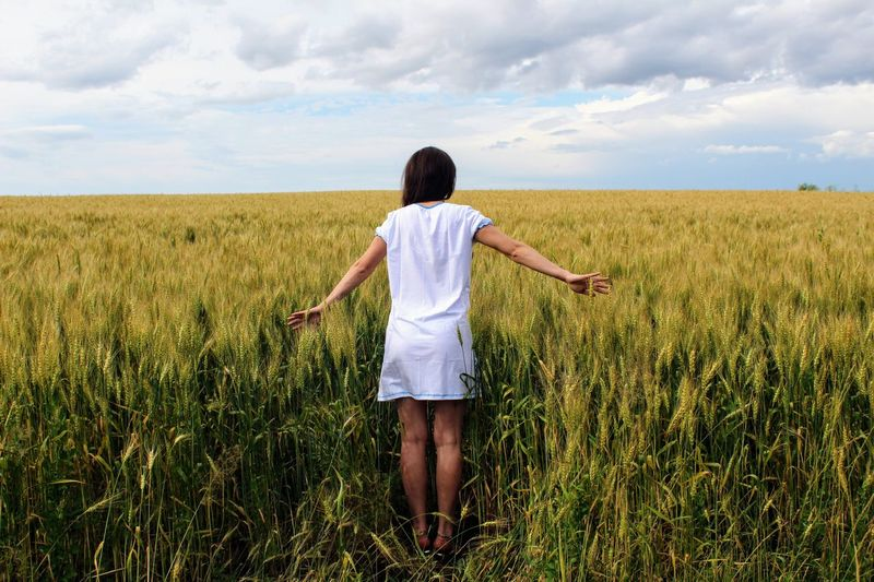 Rear View Of Woman Standing In Field Against Sky