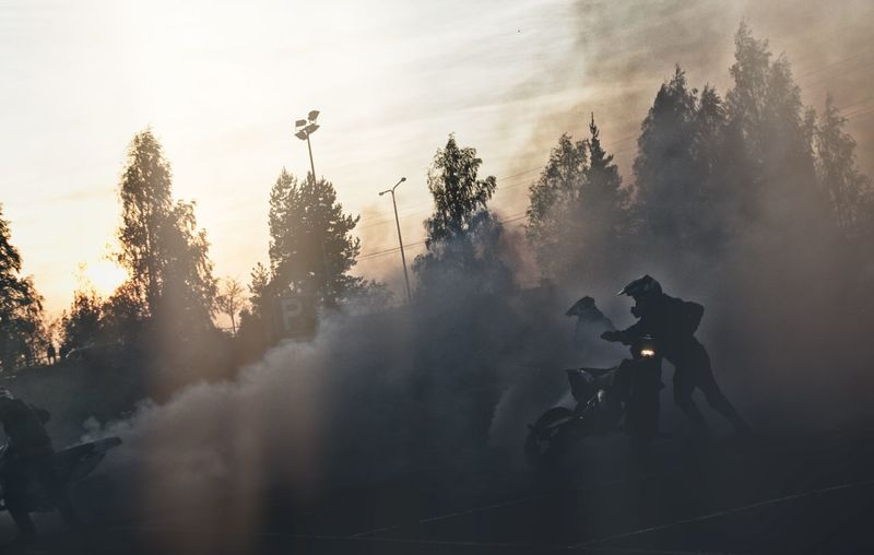 Motocross riders among smoke