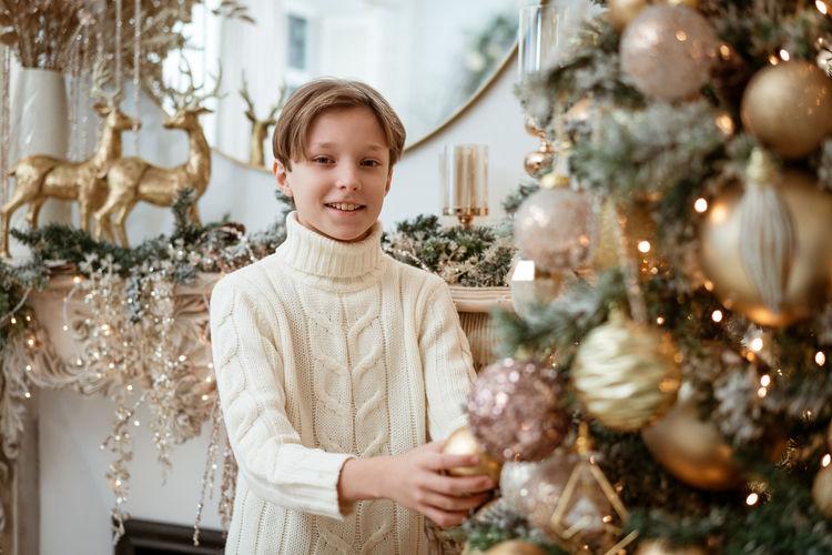 Boy decorates christmas tree at home