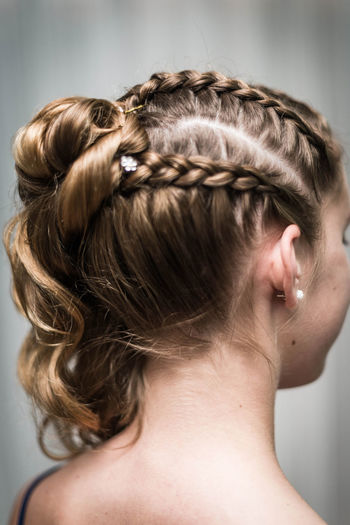 Close-up of woman with braided hair against gray background