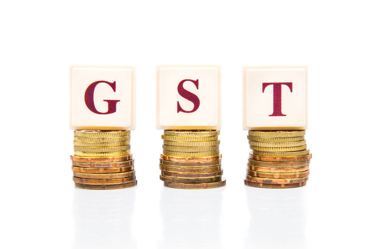 GST of Goods and Services Tax concept with a stack of gold colored coins on white background Currency Economy Government Revenue Accounting Alphabet Business Close-up Coin Conceptual Currency Finance Gold Goods And Services Tax Gst Income Income Tax Investment No People Savings Spending Studio Shot Tax Wealth White Background
