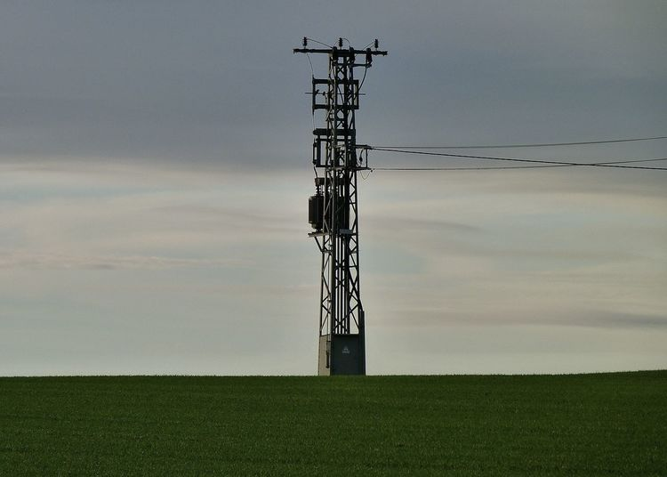 Electricity pylon on field against sky