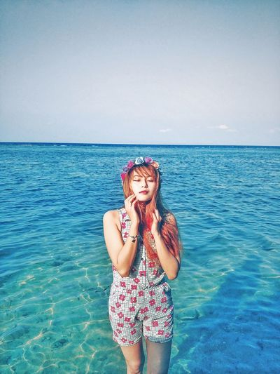 Beautiful woman wearing tiara with eyes closed standing in sea against sky