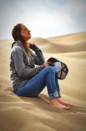 Side view of woman sitting on sand