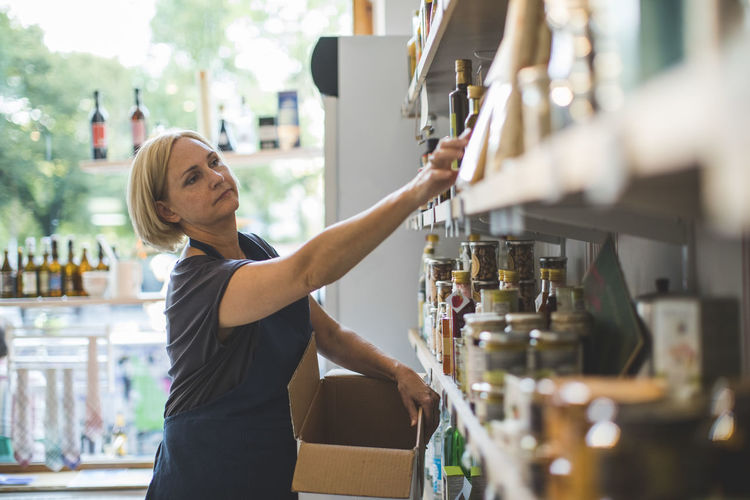 Mature female employee arranging bottles on shelf in deli