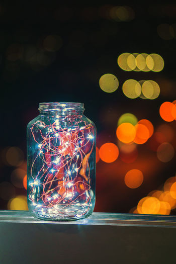 Close-up of lighting equipment on glass jar on table
