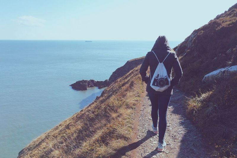Woman Walking On Pathway By Calm Blue Sea