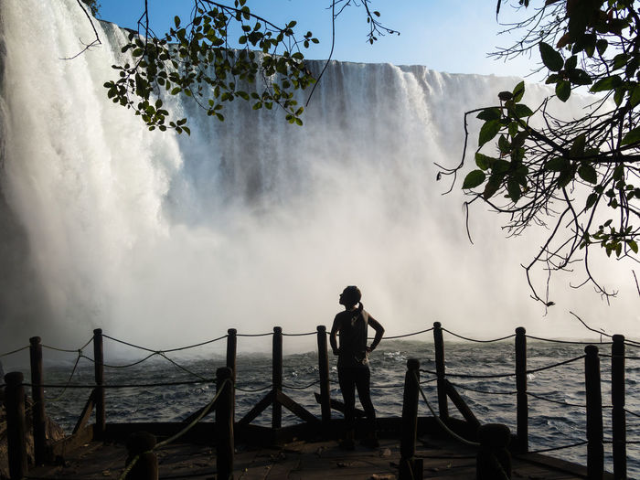 Rear view of silhouette of woman standing against lumangwe waterfall, zambia