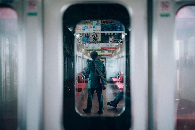 Rear view of man seen through train window