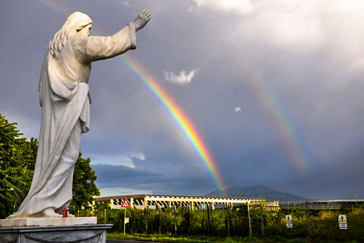 Low angle view of statue against rainbow in sky