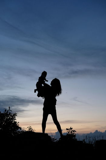 Silhouette man with woman standing against sky during sunset