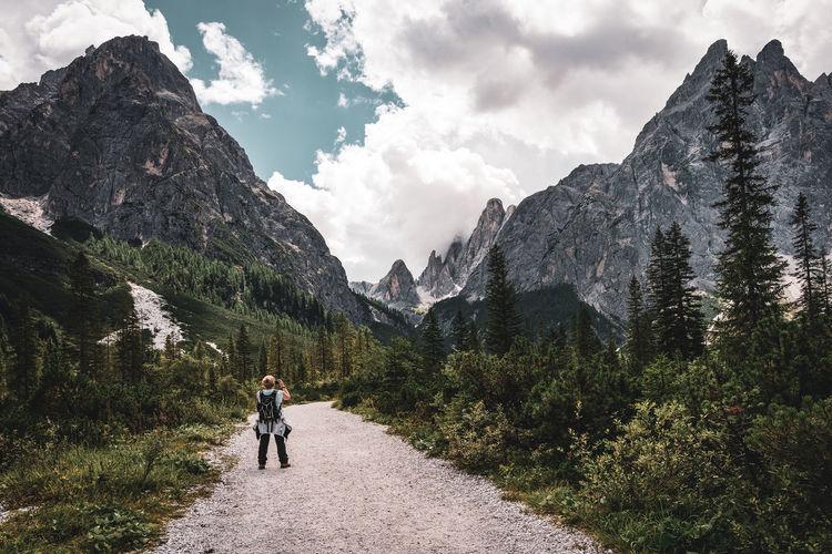 Rear view of women walking on mountain against sky