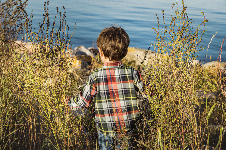 Rear view of boy standing by lake