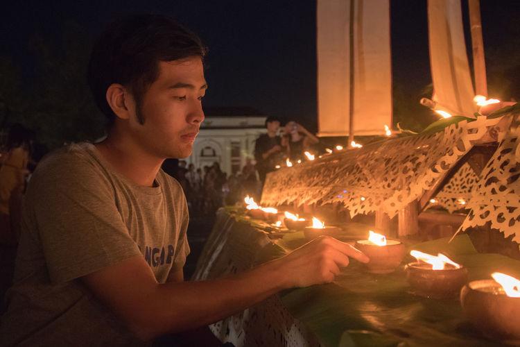 Man Holding Lit Diya During Diwali Celebration