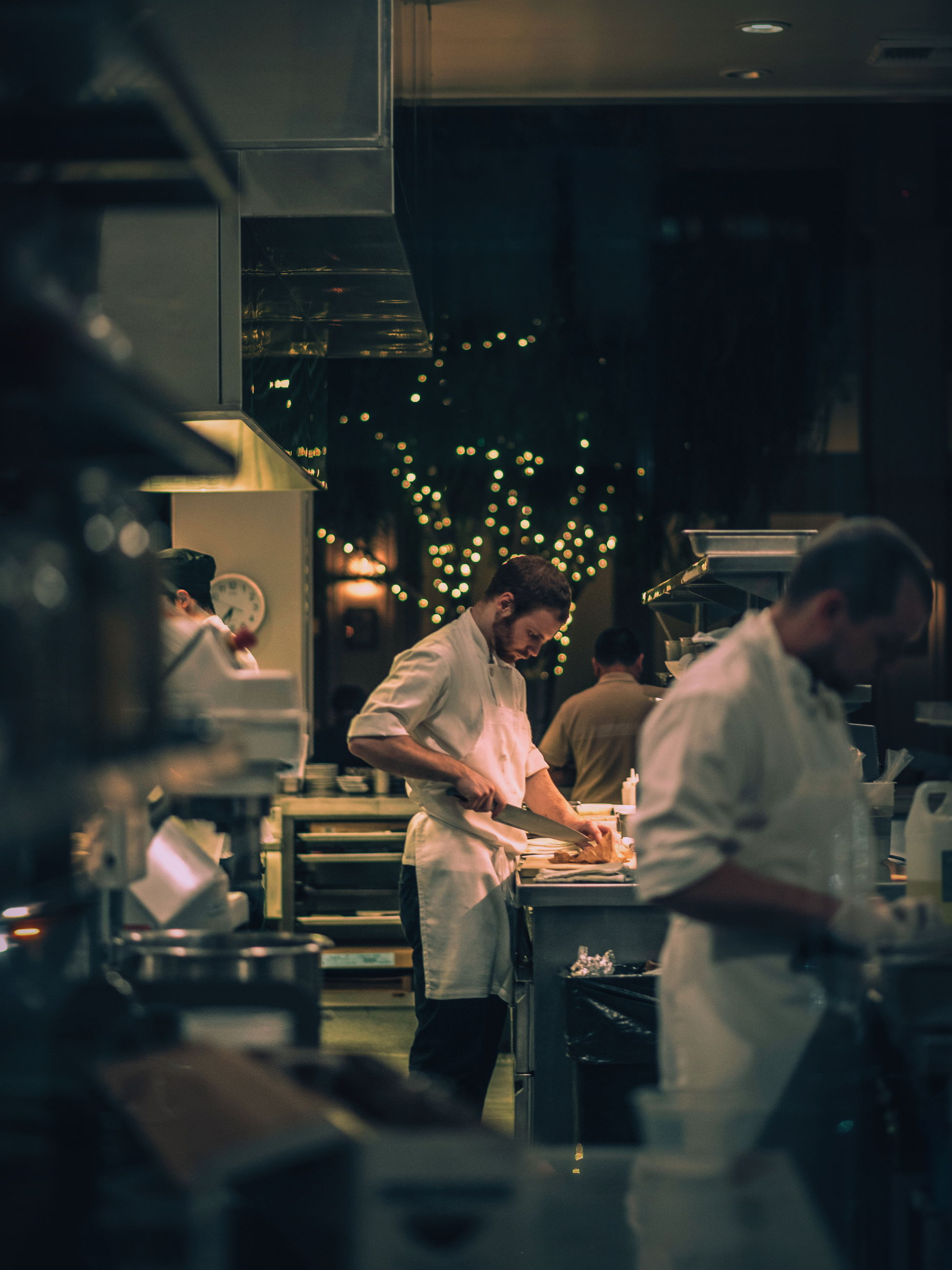 real people, mid adult men, restaurant, indoors, standing, food and drink industry, men, coworker, uniform, young adult, occupation, two people, togetherness, night, bartender, illuminated, food and drink establishment, young women, commercial kitchen, working, teamwork, adult, people