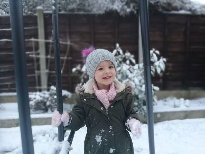Portrait Of Smiling Girl Standing By Swing During Winter