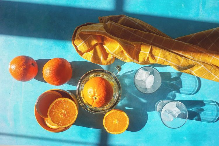 Fresh squeezed orange juice Orange Juice Directly Above Light And Shadow Fresh Turquoise Colored No People Still Life Orange Color Food And Drink Indoors  Food Blue Close-up Sunlight Table High Angle View Orange - Fruit Healthy Eating Orange Freshness Citrus Fruit Shadow