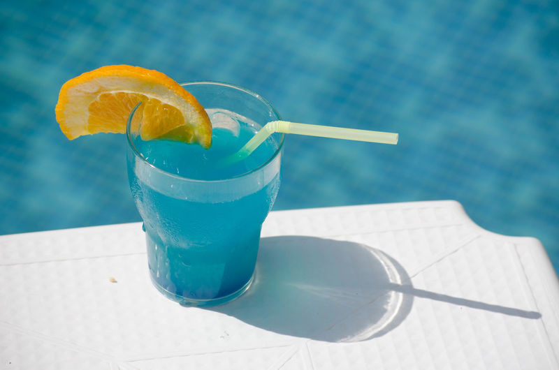 Blue cocktail glass at pool with orange Alchohol Beverage Blue Blue Drink Close-up Cocktail Cold Color Colorful Contrast Drink Fresh Freshness Fruit Glass Ice Lemon Luxury Orange Party Pool Refreshment Straw Table Travel