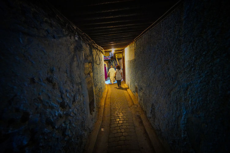 follow Travel Destinations Travel Photography Digital Nomad EyeEmNewHere Morocco Fes Morocco Direction The Way Forward Architecture Rear View Tunnel Walking Built Structure One Person Wall - Building Feature Wall Footpath Full Length Men Narrow Illuminated Indoors  Day Diminishing Perspective Light At The End Of The Tunnel Alley