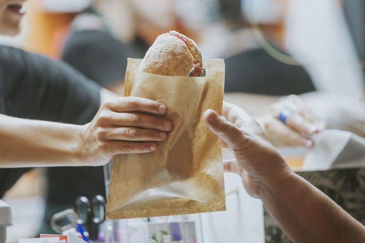 Sandwich being passed to a customer from a food truck.