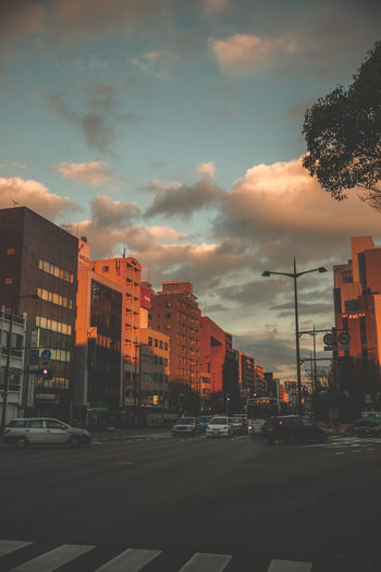 Street amidst buildings against sky during sunset