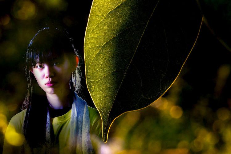 Portrait of teenage girl standing by leaf