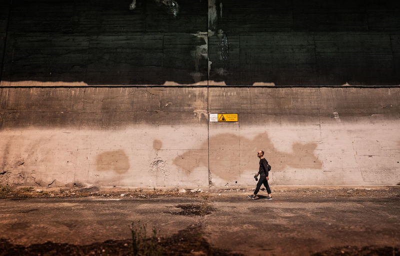 Side view full length of man walking by wall on street