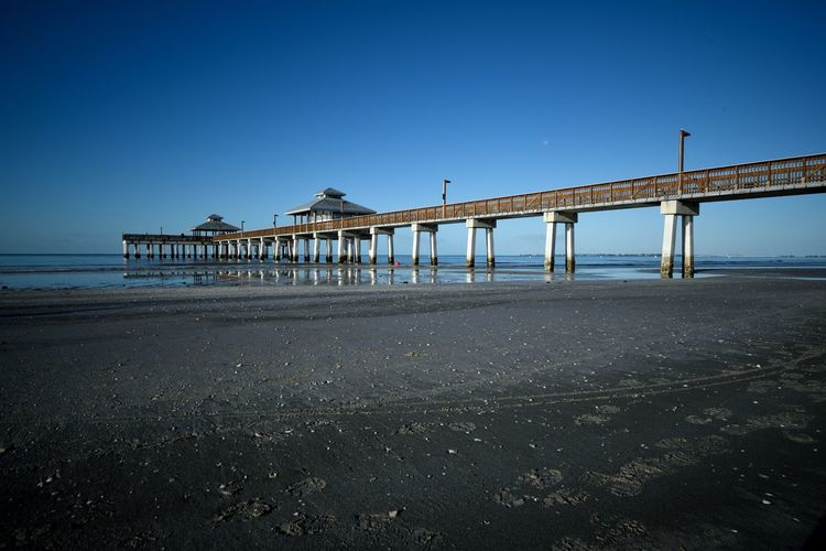 Pier of Fort Myers Beach Gulf Coast USAtrip USA Florida Nature Florida Fort Myers Beach Clear Sky Beach Built Structure Architecture Blue Sand Water Sea Copy Space Day Bridge - Man Made Structure No People Nature Scenics Travel Destinations Beauty In Nature Outdoors Tranquility