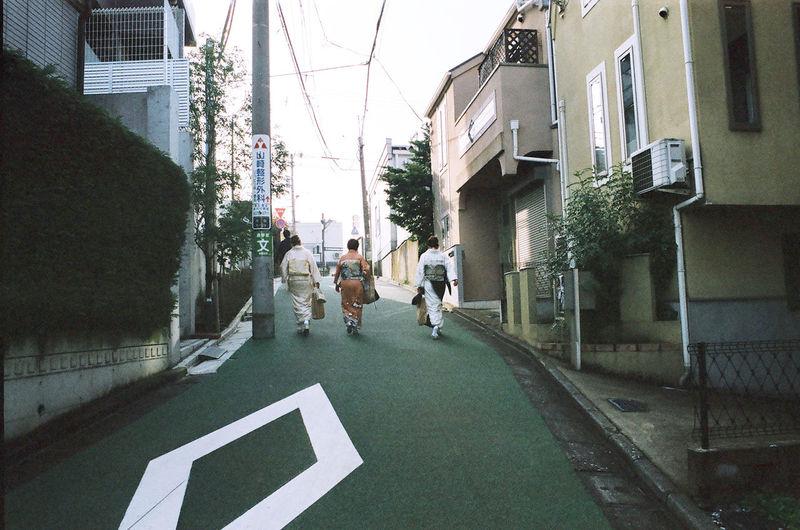Rear view of people walking on road amidst buildings