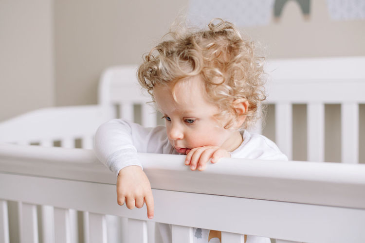 Lonely thoughtful baby boy toddler standing in crib at kids nursery room at home.