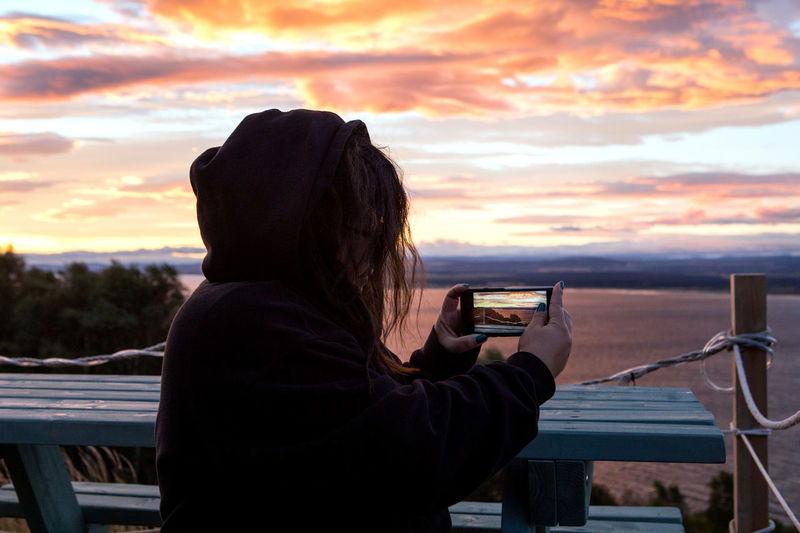 Woman Photographing Sea Against Sky During Sunrise